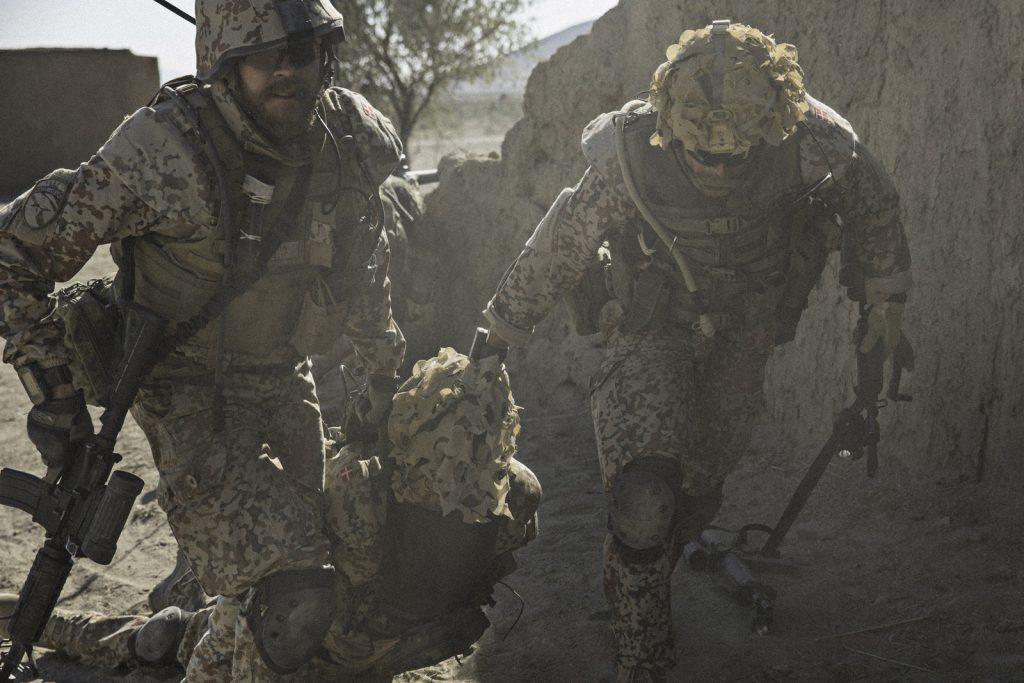 Nach einem Angriff der Taliban zieht Claus Michael Pedersen (Pilou Asbaek) mit einem seiner Männer den verletzten Lasse (Dulfi Al-Jabouri) aus der Schusslinie.